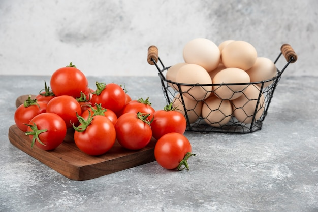 Basket of fresh uncooked eggs and ripe tomatoes on marble.