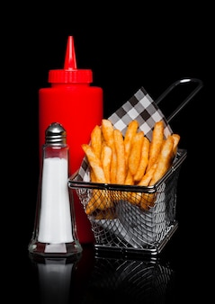 Basket of freshly made southern fries with ketchup and salt black paper on black studio background