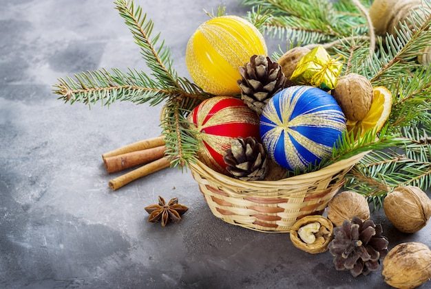 Basket full of christmas attributes and present boxes on a dark surface. christmas composition