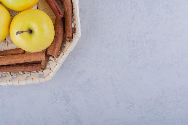 Basket full of cinnamon sticks and apples on stone table.