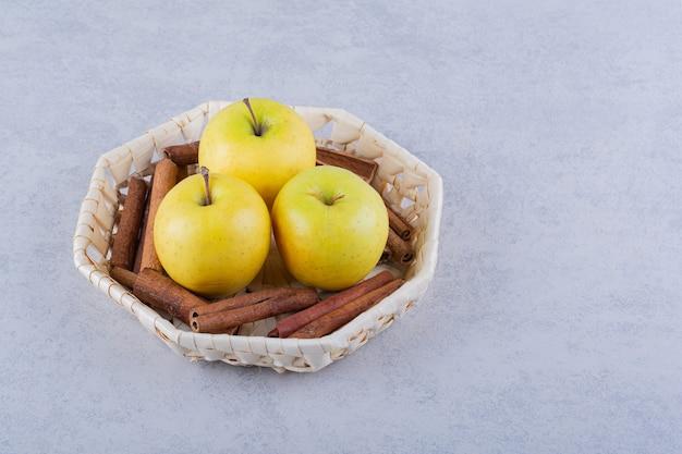 Basket full of cinnamon sticks and apples on stone.