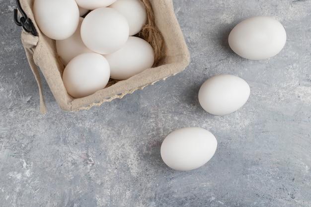 Cesto pieno di uova di gallina bianche fresche su una biglia.