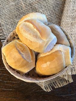 木製のテーブルの上のパンでいっぱいのバスケット