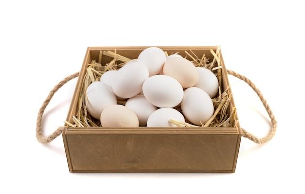 わら側のビューに横になっている鶏の卵がいっぱい入ったかご。