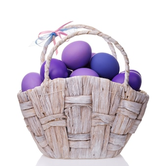 白い背景で隔離の紫の色合いで着色された卵でいっぱいのバスケット