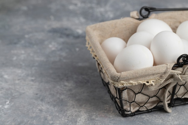 Корзина, полная свежих белых куриных яиц на мраморном фоне.