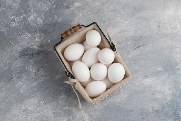 大理石の上の新鮮な白い鶏の卵でいっぱいのバスケット。