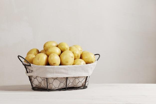 テキストのための場所が付いている木製のテーブルの上の新鮮な、若いジャガイモでいっぱいのバスケット。