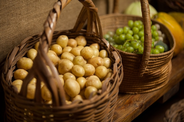 カウンターでブドウとジャガイモがいっぱい入ったかご
