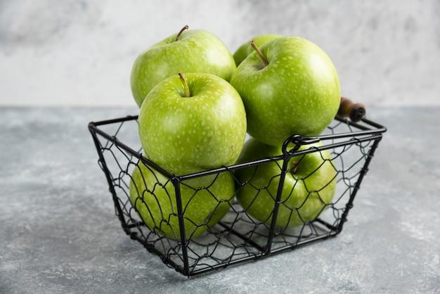 대리석 테이블에 반짝이는 녹색 사과가 가득한 바구니.