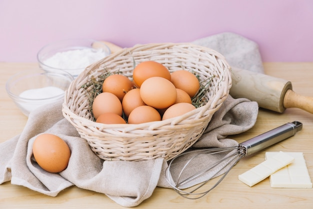 Basket full of whole eggs; flour; sugar; white chocolate; whisks and rolling pin on wooden desk