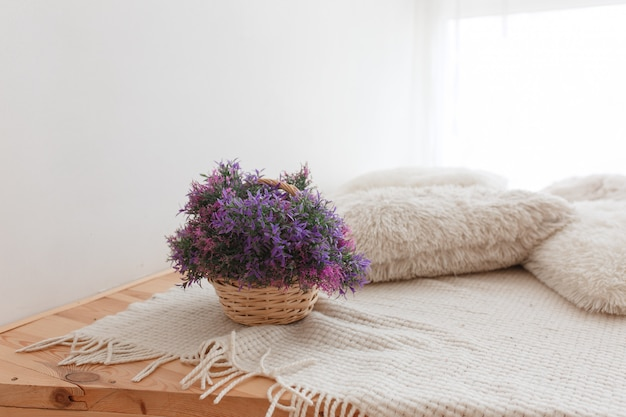 Basket of jute with purple flowers wooden floor with knitted pillows and covering