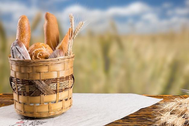 麦畑を見下ろす古い素朴な木製のテーブルの上の各種の新鮮な無愛想なロールパンとパンのバスケット