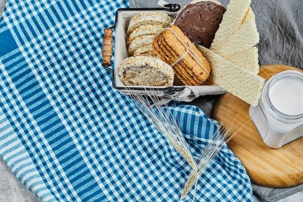 비스킷 바구니와 식탁보와 대리석 테이블에 우유 한 병.