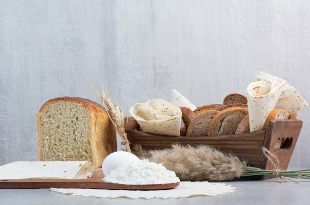 Корзина хлеба и лаваша на мраморном фоне. фото высокого качества