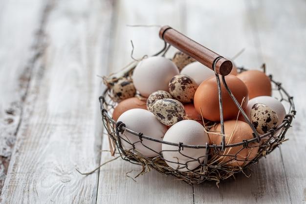 Корзина красочных свежих яиц на деревянном столе