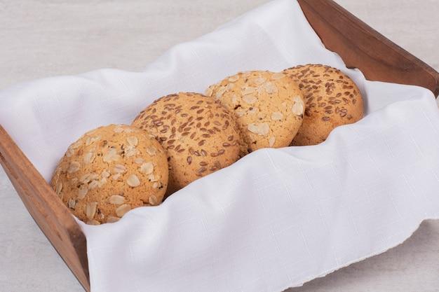 Корзина печенья с кунжутом на белой поверхности.