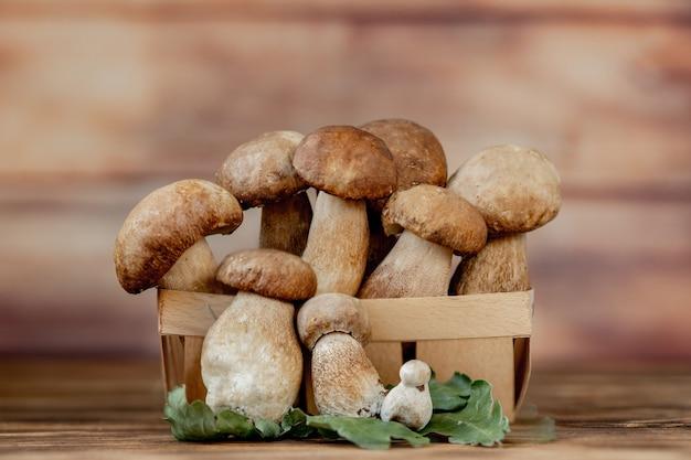 Корзина съедобных грибов: подберезовики и подберезовики, деревенский деревянный фон, выборочный фокус, тонированное изображение.