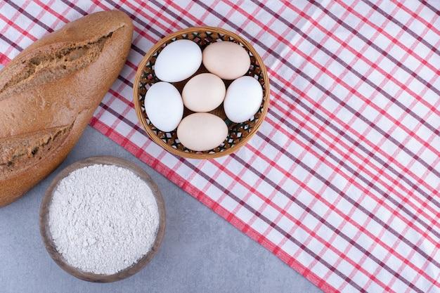 계란 바구니, 바톤 빵 한 덩어리 및 대리석 표면에 밀가루 한 그릇