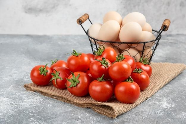 Корзина свежих сырых яиц и спелых помидоров на мраморе.