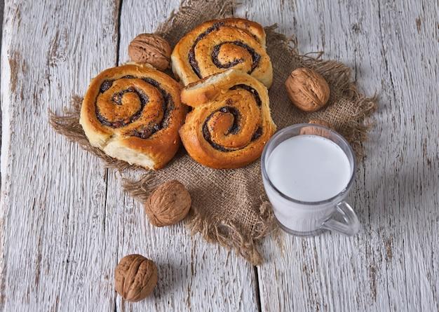 호두와 우유 한잔과 함께 오래 된 나무 테이블에 제공 잼 수제 빵 바구니