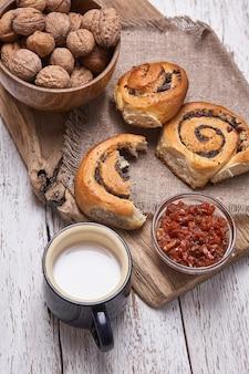 호두와 우유 한잔과 함께 오래 된 나무 테이블에 제공되는 잼으로 만든 빵 바구니