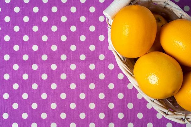 Корзина лимонов на точечной фиолетовой скатерти