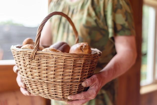 Корзина с белыми грибами в руках мужчины