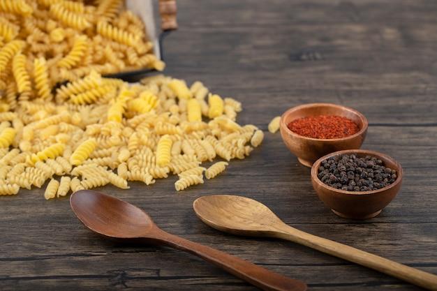 Корзина сырых макаронных изделий fusilli с перцовыми специями на деревянном столе.