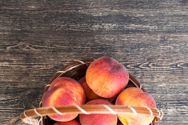 キッチンの黒いテーブルの上に、熟した赤とジューシーな桃のバスケット
