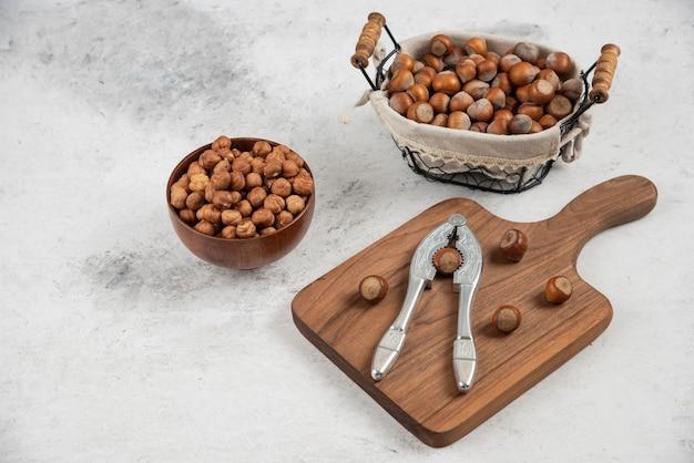 껍질을 벗긴 헤이즐넛 바구니와 대리석 테이블에 있는 너트 크래킹 도구.
