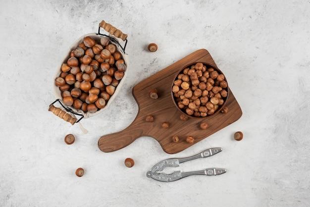 도마 옆에 껍질을 벗긴 헤이즐넛, 커널 및 너트 크래킹 도구 바구니.