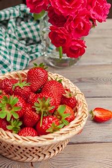 Корзина урожая клубники на деревянном столе крупным планом