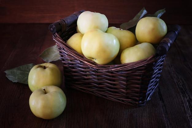 맛 있는 노란 사과 바구니입니다. 수확의 상징적인 이미지입니다. 건강한 영양에 대한 개념입니다. 나무 배경입니다. 전면보기. 공간을 복사합니다.