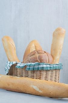 Корзина различного хлеба на мраморной предпосылке. фото высокого качества