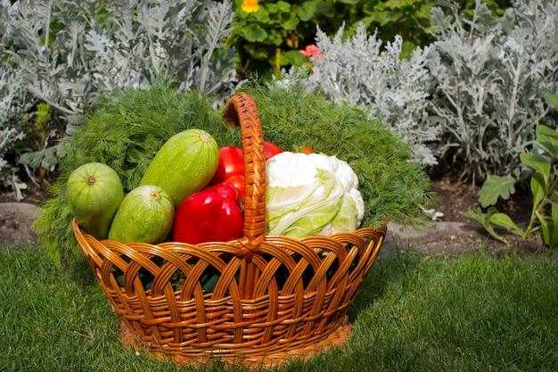 花を背景に緑の芝生の上の野菜のバスケット