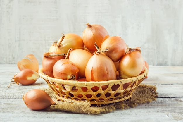 Basket of onion medium size on wooden background. selective focus.