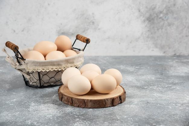 Cesto di uova crude fresche organiche poste sulla superficie di marmo.