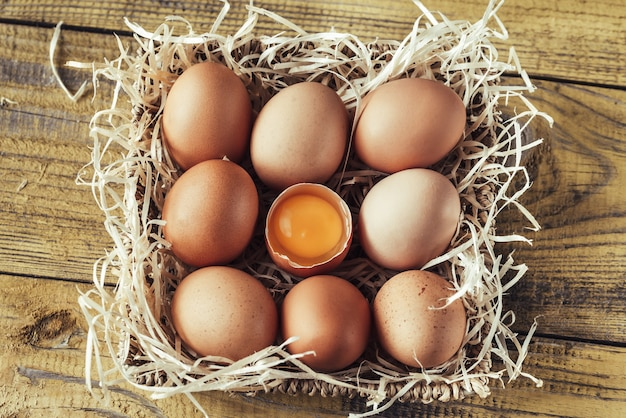 Basket of raw chicken eggs on the wooden table