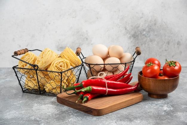 Cesto di spaghetti crudi, pomodori, peperoncino e uova sulla superficie in marmo.