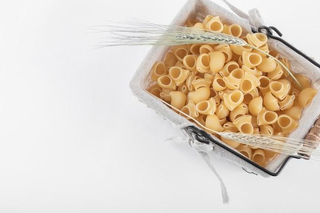 Cesto di pasta cruda con spighe di grano su bianco.