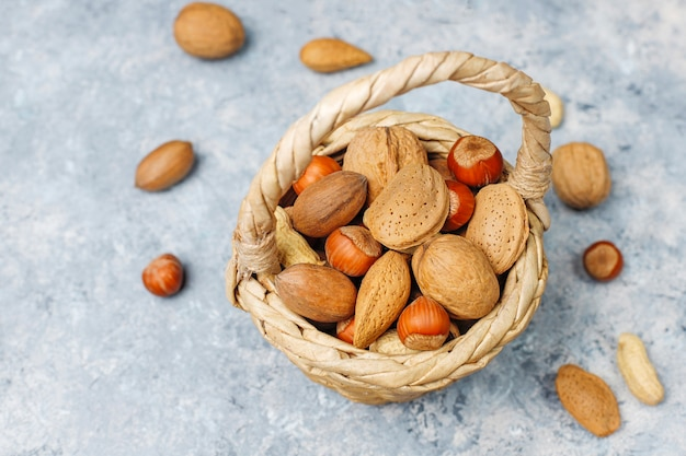 Basket reach in various kinds of nuts in shells, peanuts, almonds, hazelnuts and walnuts on concrete surface