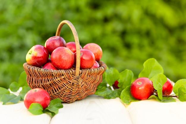 Корзина красных яблок с зелеными листьями на деревянных фоне. сбор урожая