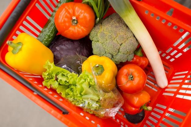 Корзина красного цвета с овощами и зеленью в магазине. перец, брокколи, лук, салат, помидоры, капуста.