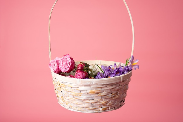 Basket of spring flowers isolated on pink