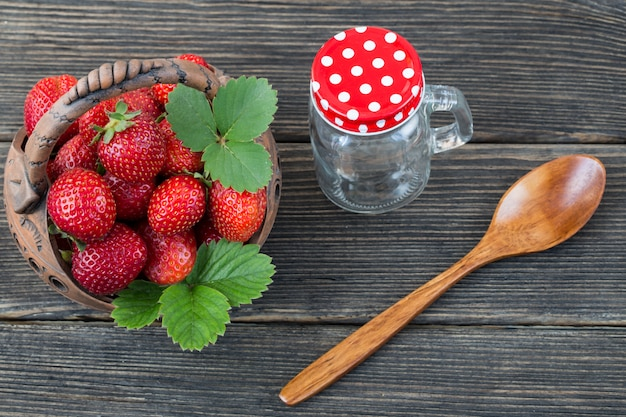In a basket strawberries close-up, spoon and glass jar