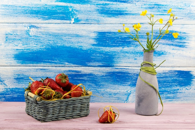 A basket of strawberries and a vase of wildflowers.
