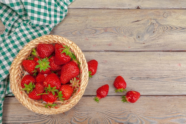 Basket of strawberry harvest on wooden surface table close up
