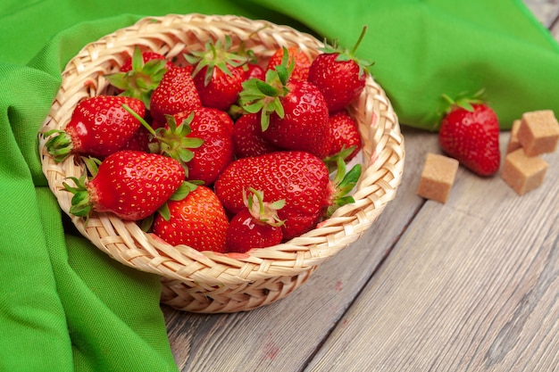 Basket of strawberry harvest on wooden table close up