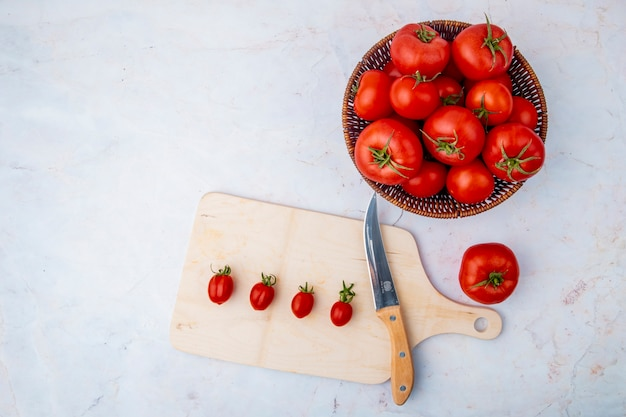 Basket of tomatoes and cutting board on white surface